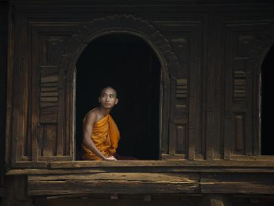 A Monk Out from the Windows of a Wooden Monastery in Myanmar