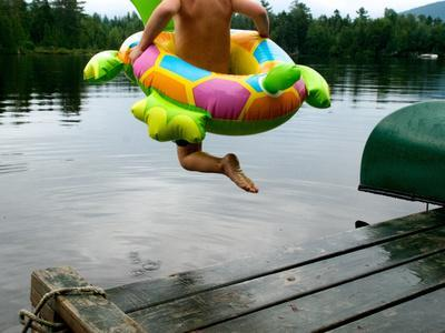 A Boy Jumps from a Dock into the Water