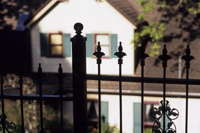 A Wrought Iron Black Fence Frames a Home with Blue Shuttered Windows