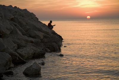 A Man Fishing at Sunrise on the Beach at Larnaka, Cyprus