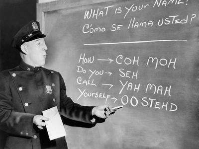 NYC Police Officer Practices Basic Spanish Phrases Written on Blackboard, Ca. 1955