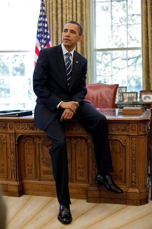 President Barack Obama Sits on the Edge of the Resolute Desk in the Oval Office, April 30, 2010