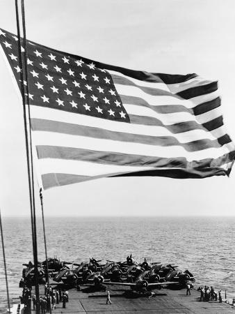 U.S. Flag Waving in Foreground over Flight Deck of an Escort Carrier, July 16, 1943