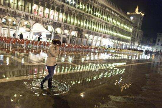 A Woman Walks in Piazza San Marco During High Tide in
