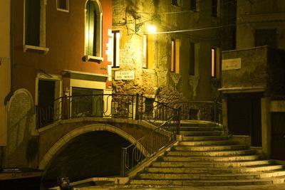 A Stairway and Bridge Over a Canal At Night