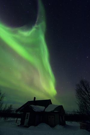 The Aurora Borealis Over a House in a Sami Village