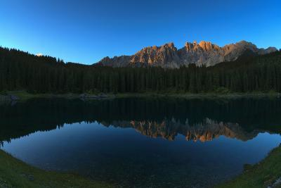 A Clear Lake Edged with Forests Near Latemar Mountain and the Dolomites