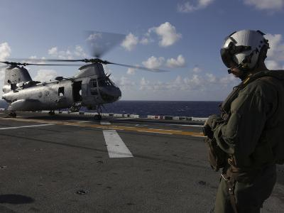 A Crew Chief Watches a CH-46E Sea Knight Helicopter Aboard USS Makin Island