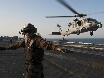 Airman Checks For a Clear Deck As An MH-60S Sea Hawk Takes Off USS John C. Stennis