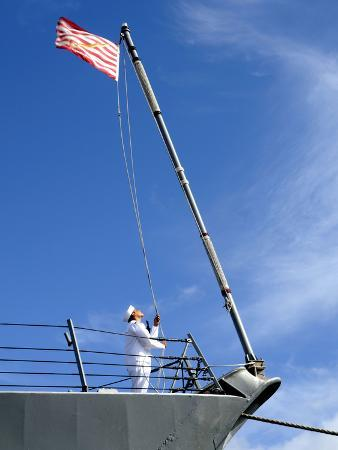 A Sailor Lowers the U.S. Navy Jack Aboard USS Chafee