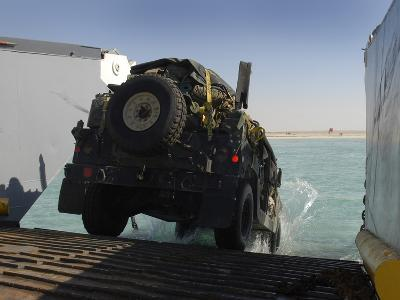 A Humvee Drives Down the Ramp of a Landing Craft Utility