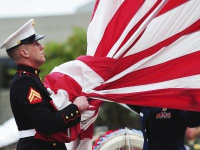 A United States Marine Takes the American Flag Into His Hands Before Folding It