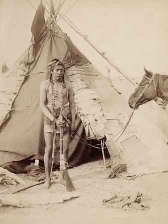 A Native American Stands at the Entrance to His Teepee Holding a Rifle, 1880-90