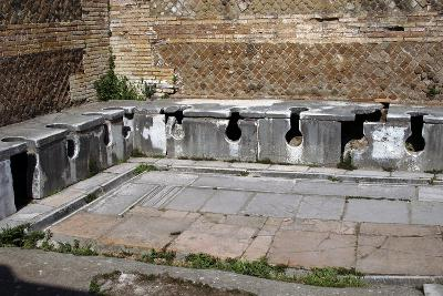 Ostia Antica. Latrine at the Domus of Triclini, Headquarters of the Guild of Builders. 2nd…