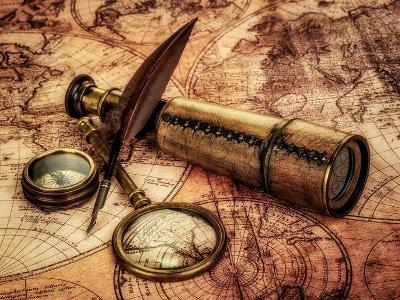 Vintage Magnifying Glass, Compass, Goose Quill Pen And Spyglass Lying On An Old Map