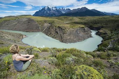 Woman Sitting Above a River Bend in Front of the Torres Del Paine National Park