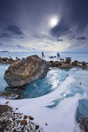 Expedition team members trek over blue glacial ice.