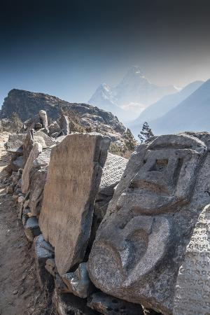 Mani Stones on a trail with Mt. Ama Dablam in background, Nepal.