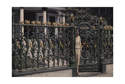 A Woman Stands Next to a Metal Fence Designed after Stalks of Corn