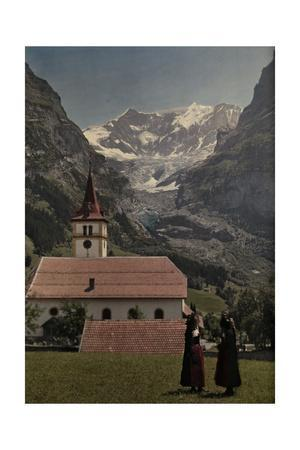Women Talk in a Field in Front of a Church at the Foot of the Glacier