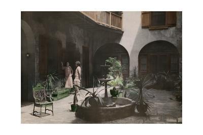 Two Women Talk in a French Quarter Courtyard