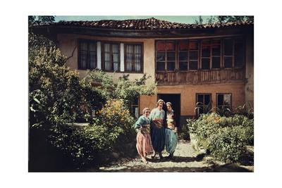Three Women in Traditional Serbian Clothing in Front of their Home