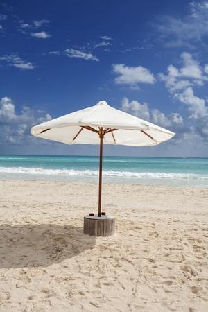 A White Beach Umbrella Stands Beside the Caribbean Sea