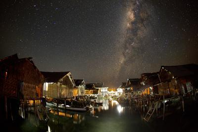 The Milky Way Stretches Above the Warm Glow of Sampela at Night