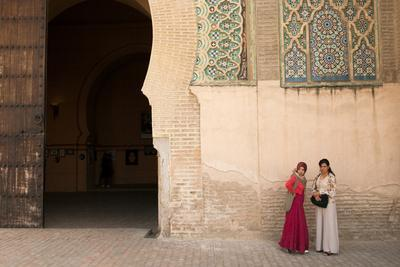 Two Young Girls Stand Alongside a Wall Near a Gateway Entrance in Meknes, Morocco