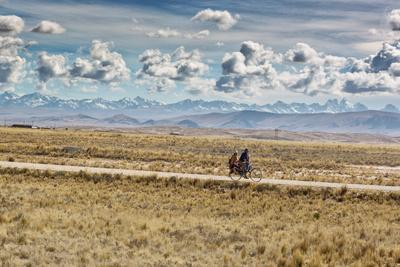 A Man Cycles with a Family Member on the Back of His Bicycle Between La Paz and Tiwanaku