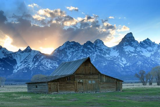 At Sunset The Teton Range Rises Behind A Historic Barn On
