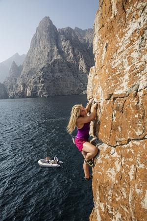 Watched by a Teammate, a Climber Scales a Cliff Rising from the Gulf of Oman