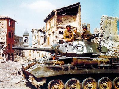 An American Sherman Tank with Three Soldiers Passing Through a Town, Italy, 1943