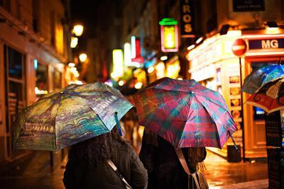 People Strolling Through the Rainy Streets at Night in Paris, France