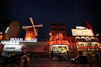The Famous Moulin Rouge, a Cabaret in Paris, Is Illuminated in Red and Yellow at Night