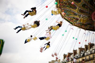 Adults and Children Enjoy a Swing Ride in Paris, France