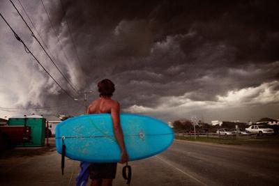 A Man Carries His Surfboard Along the Street by the Outer Banks of North Carolina