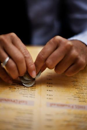 A Man Holds Coins in His Hand While Looking at a Restaurant Menu in Paris, France