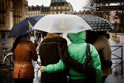A Couple Embrace under an Umbrella Outside the Notre Dame in Paris, France