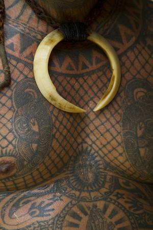 A Body Tattoo and a Tusk Necklace on a Man's Chest