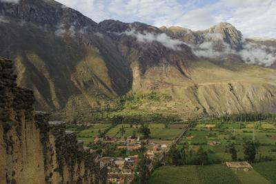 An Inca Stone Wall Frames a View of Green Fields