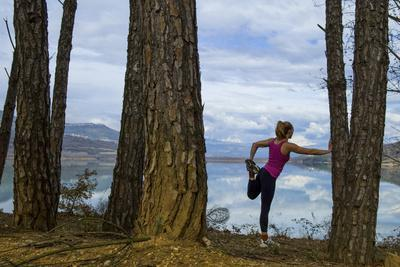 A Woman Stretching Among Large Pine Trees after a Run