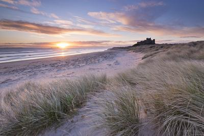 Sunrise over Bamburgh Beach and Castle from the Sand Dunes, Northumberland, England. Spring (March)