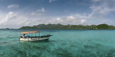 An Outboard Motorboat Adrift in a Clear Blue Water Off Crab Caye