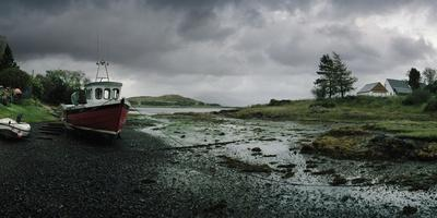 A Boat Rests on a Mud Flat at Low Tide