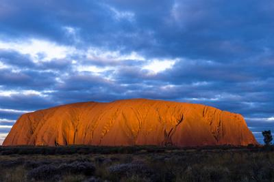 The Last Sunrays of Sunset Illuminate the Sandstone Massive of Uluru on the Desert Plain