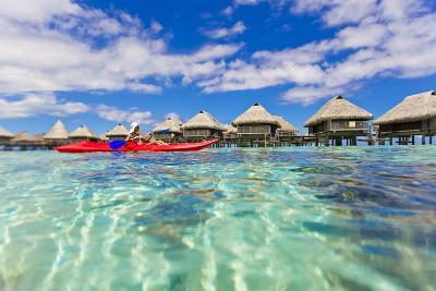 A Woman Kayaking in the Ocean at a Resort with Over-The-Water Bungalows