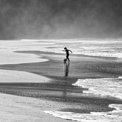 A Young Boy Kicks a Ball on Itamambuca Beach in Ubatuba, Brazil