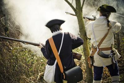 Historical Reenactment: American Volunteers (Patriots) Firing on British Army. American Revolutiona