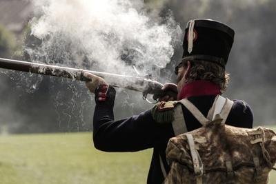 Historical Reenactment: Soldier from Napoleon's Line Infantry Firing Muzzle-Loading Flintlock Rifle
